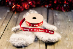 Knitted mittens with ribbon decoration With love on wooden backg stock photos