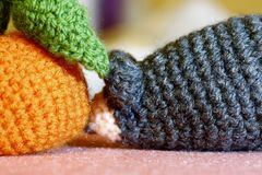Knitted mouse toy with fruit. Woolen knitted mouse with handmade orange fruit Stock Images