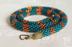 Knitted necklace from beads of emerald and orange color Stock Photos