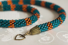 Knitted necklace from beads of emerald and orange color Royalty Free Stock Image