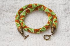 Knitted necklace from beads of light green and orange color Royalty Free Stock Photos