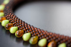 Knitted necklace from big and small beads on a wooden surface Royalty Free Stock Photos