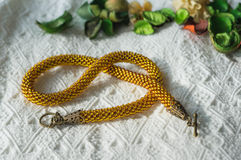 Knitted necklace from brilliant yellow beads Royalty Free Stock Photo