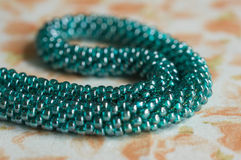 Knitted necklace of color aquamarine from beads Stock Photo