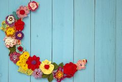 A knitted necklace of colorful flower. S is lying on blue wooden boards royalty free stock photo