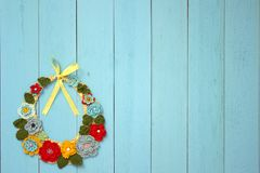 A knitted necklace of colorful flowers is lying on wooden boards. A knitted necklace of colorful flowers is lying on blue wooden boards stock photo