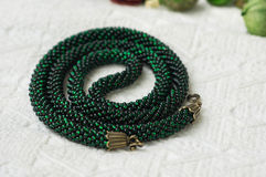 Knitted necklace from green beads Royalty Free Stock Photos