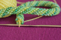 Knitted necklace from yellow and green beads Stock Image