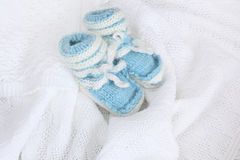 Knitted newborn baby booties on crocheted blanket white background Royalty Free Stock Images