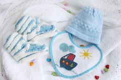 Knitted newborn baby booties, hat and bib on crocheted blanket white background with colorful hearts. Blue knitted newborn baby booties, hat and bib on crocheted royalty free stock images