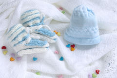 Knitted newborn baby booties and hat on crocheted blanket white background with colorful hearts. Blue knitted newborn baby booties and hat on crocheted blanket stock photo