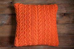 Knitted orange cushion. On a wooden background royalty free stock photo