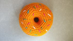 Knitted orange donut with dressing on the background of boxes closeup. Handmade for children playing in a store or cafe. royalty free stock image