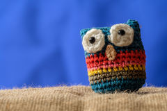 Knitted owl amulet. Knitted wool owl from colored threads, a mascot for smart Royalty Free Stock Photo