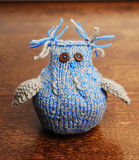 Knitted owl on a wooden background. Gray-blue knitted owl on a wooden brown background Stock Images