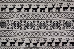 Knitted pattern with deer and snowflakes. Background Stock Images