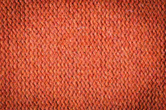 Knitted pattern. Orange knitted background of loops Stock Photos