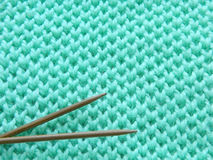 Knitted pattern spokes `Honeycomb`. Turquoise, mint pattern with needles Stock Images