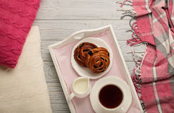 Knitted pillows and plaid, buns and coffee on a light wooden background. Top view. Flat lay royalty free stock images