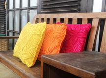 Knitted pillows on a wooden bench Stock Images