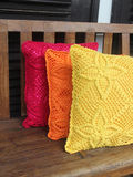 Knitted pillows on a wooden bench Stock Photos