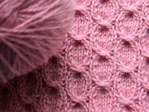 Knitted pink pattern. Pink Knitted pattern with the help of needles and a ball of yarn Stock Photo