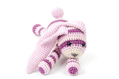 Knitted pink rabbit toy lays isolated on white Stock Image