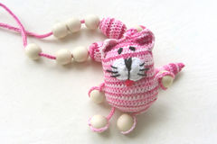 Knitted pink striped handmade crafted cat. Children`s toy. Crochet pattern. Handicraft manufacturing Royalty Free Stock Image