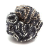 Knitted pompom of variegated yarn Royalty Free Stock Photos