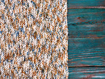Knitted product carpet plaid close up of fiber of thread texture wool wooden background board floor brown green Stock Photo
