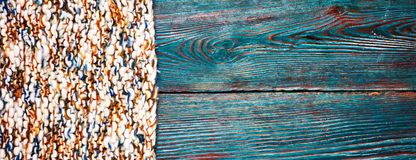 Knitted product carpet plaid close up of fiber of thread texture wool wooden background board floor brown green.  royalty free stock image