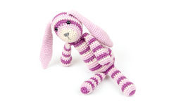 Knitted rabbit toy is sitting isolated on white Stock Image