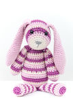 Knitted rabbit toy sitting over white background Stock Photo