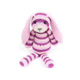 Knitted rabbit toy is sitting over white background Stock Photo