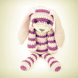 Knitted rabbit toy sitting over white background Stock Images
