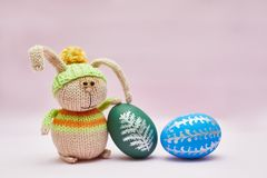 Knitted rabbit and two Easter eggs for a postcard. stock photo