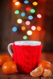 Knitted red cup with christmas lights at background Stock Photos