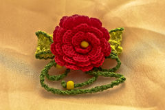 Knitted red flower. Hand-made knitted red flower brooch with green leaves on biege organza background Stock Photos