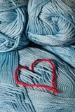 Knitted red heart on blue Stock Photography