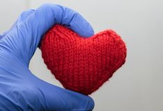Knitted red heart holding a hand in medical gloves. Warm knitted red heart holding a hand in medical gloves royalty free stock photography
