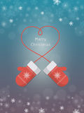 Knitted red mittens on winter background. Christmas greeting card with mittens on blue background. Knitted red mittens with rope in the form of heart. Christmas Stock Photo