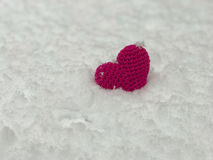 Knitted red threads red heart lies on the snow Royalty Free Stock Photos