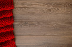 Knitted reddish blanket on a wooden background with copy space Royalty Free Stock Photography