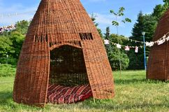 Wickers hut in park. Huts from woven vegetable twigs placed in the public park for people to relax in summer season Stock Photo