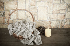 Knitted scarf in the basket and color candle on wooden table opp Stock Photo