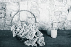 Knitted scarf in the basket and color candle on wooden table opp Stock Images