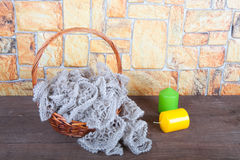 Knitted scarf in the basket and two color candles on wooden tabl Royalty Free Stock Images