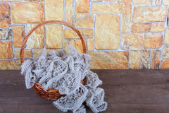 Knitted scarf in the basket and two color candles on wooden tabl Stock Photos