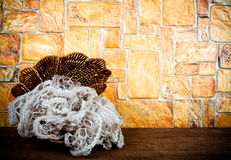 Knitted scarf in the basket and two color candles on wooden tabl. E opposite a stony wall. Toned Stock Photography
