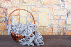 Knitted scarf in the basket on wooden table opposite a stony wal Stock Photography